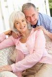 Pares mayores que se relajan junto en el sofá imágenes de archivo libres de regalías