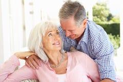 Pares mayores que se relajan junto en el sofá foto de archivo