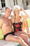 Pares mayores que se relajan por la piscina al aire libre Foto de archivo libre de regalías