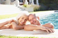 Pares mayores que se relajan por la piscina al aire libre fotografía de archivo