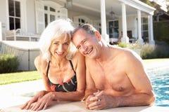 Pares mayores que se relajan por la piscina al aire libre foto de archivo
