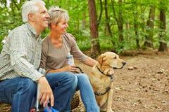 Pares mayores que se sientan con el perro en bosque Foto de archivo libre de regalías