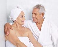Pares mayores que se sientan en balneario en días de fiesta Imagenes de archivo