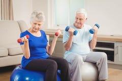 Pares mayores que se sientan en bolas de la aptitud con pesas de gimnasia Fotografía de archivo