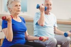 Pares mayores que se sientan en bolas de la aptitud con pesas de gimnasia Foto de archivo