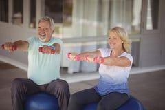 Pares mayores que se sientan en bolas de la aptitud con pesas de gimnasia Imágenes de archivo libres de regalías