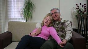Pares mayores que se sientan en el sofá almacen de metraje de vídeo