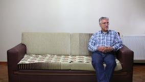 Pares mayores que se sientan en el sofá metrajes