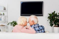 pares mayores que se sientan en el sofá delante de la TV foto de archivo libre de regalías