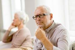 Pares mayores que se sientan en el sofá en casa Foto de archivo