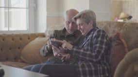 Pares mayores que se sientan en el sofá grande y el hombre calvo que muestran las fotos en el teléfono móvil para su mujer con el almacen de metraje de vídeo
