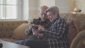Pares mayores que se sientan en el sofá grande y el hombre calvo que muestran las fotos en el teléfono móvil para su mujer con el metrajes