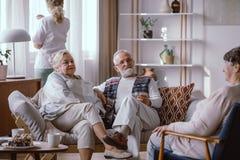 Pares mayores que se sientan en el sof? en la cl?nica de reposo foto de archivo