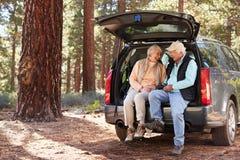 Pares mayores que se sientan en el tronco de coche abierto que se prepara para un alza Imágenes de archivo libres de regalías