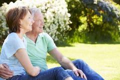 Pares mayores que se sientan en jardín del verano junto imagen de archivo