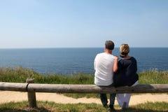 Pares mayores que se sientan en la cerca que mira el océano imagen de archivo