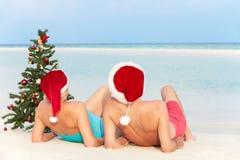 Pares mayores que se sientan en la playa con el árbol de navidad y los sombreros Fotos de archivo