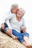 Pares mayores que se sientan en la playa junto Foto de archivo