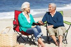 Pares mayores que se sientan en la playa que tiene comida campestre Foto de archivo