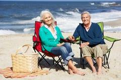 Pares mayores que se sientan en la playa que tiene comida campestre Imagen de archivo
