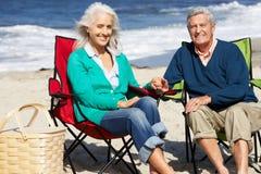Pares mayores que se sientan en la playa que tiene comida campestre Imagenes de archivo