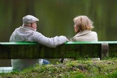 Pares mayores que se sientan en un banco Foto de archivo libre de regalías