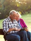 Pares mayores que se sientan en un banco de parque que mira la tableta Fotos de archivo libres de regalías