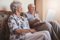 Pares mayores que se sientan en un sofá con un ordenador portátil Imagen de archivo