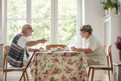 Pares mayores que se sientan junto en el té de consumición de la tabla y que comen la torta fotos de archivo