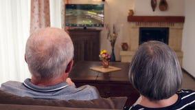 Pares mayores que se sientan junto en la televisión de observación del sofá almacen de metraje de vídeo
