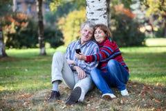 Pares mayores que se sientan junto y que hacen el selfie con el teléfono móvil en parque Fotos de archivo