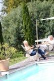 Pares mayores que se sientan por la piscina y que se relajan Fotos de archivo