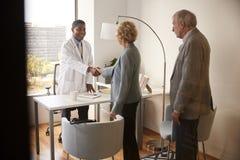 Pares mayores que son saludados por la visita masculina del doctor With Handshake On al hospital para la consulta fotografía de archivo libre de regalías