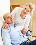 Pares mayores que sonríen junto en el sofá en hogar Fotografía de archivo