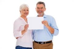 Pares mayores que sostienen el cartel en blanco fotos de archivo libres de regalías