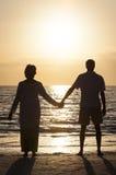 Pares mayores que sostienen la playa tropical de la puesta del sol de las manos Foto de archivo