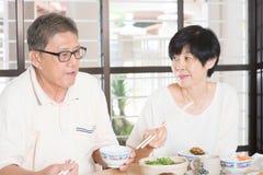 Pares mayores que tienen comida Imagen de archivo libre de regalías