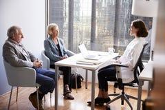 Pares mayores que tienen consulta con el doctor de sexo femenino In Hospital Office imagen de archivo