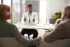 Pares mayores que tienen consulta con el doctor de sexo masculino In Hospital Office foto de archivo libre de regalías
