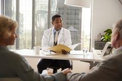Pares mayores que tienen consulta con el doctor de sexo masculino In Hospital Office fotos de archivo libres de regalías