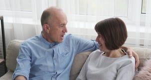 Pares mayores que tienen discusión divertida sobre el sofá almacen de metraje de vídeo