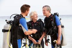 Pares mayores que tienen lección del buceo con escafandra con el instructor Imagen de archivo