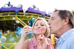 Pares mayores que tienen un buen rato en la feria de diversión Foto de archivo