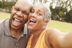 Pares mayores que toman Selfie en parque Imagen de archivo
