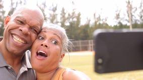 Pares mayores que toman Selfie en parque metrajes