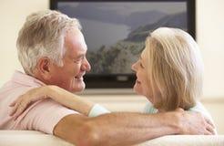 Pares mayores que ven la TV con pantalla grande en casa Imágenes de archivo libres de regalías