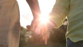 Pares mayores románticos que llevan a cabo las manos en la puesta del sol almacen de video