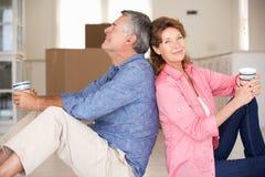 Pares mayores sentados en nuevo hogar Foto de archivo libre de regalías