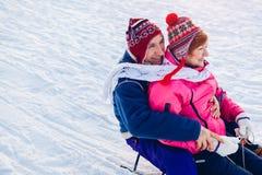 Pares mayores sledding abajo Familia que se divierte en parque del invierno Día del `s de la tarjeta del día de San Valentín fotos de archivo libres de regalías