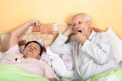 Pares mayores soñolientos en cama Imagenes de archivo